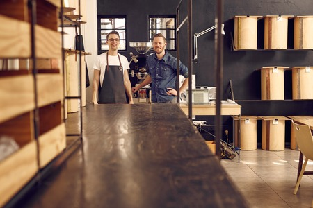 Photo pour Portrait of two men in hipster style wear, smiling at the camera confidently in their modern workspace where they roast coffee beans with neat and simple storage containers - image libre de droit