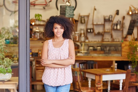 Beautiful young cafe owner proud of her small business standing smiling in the doorway of her coffee shop