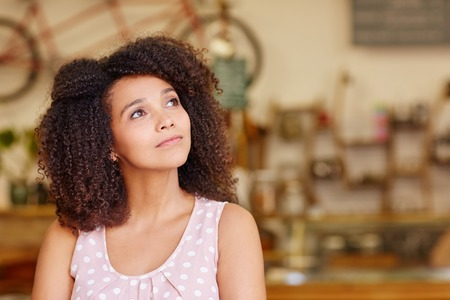 Photo pour Mixed race woman in a coffee shop looking away thoughtfully and daydreaming - image libre de droit