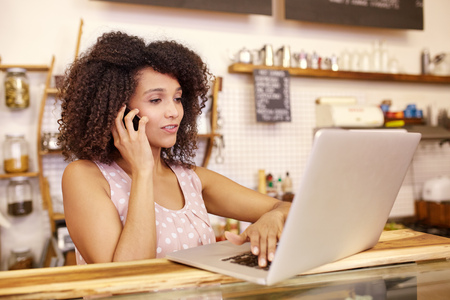 Foto per Small business owner in her coffee shop typing on her laptop while talking on the phone - Immagine Royalty Free
