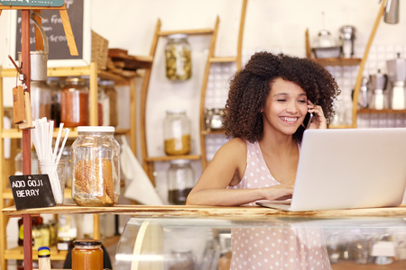 Photo pour Happy young coffee shop owner talking on he mobile phone while typing on her laptop on the counter - image libre de droit