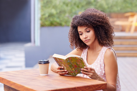 Photo pour Young mixed race woman sitting a table outdoors with her takeaway coffee reading a book - image libre de droit