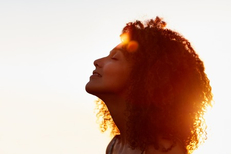 Profile protrait of a beautiful woman with afro style hair silhouetted against golden sun flare on a summer eveningの写真素材
