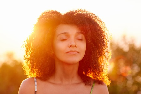 Photo pour Beautiful woman with curly afro hair looking relaxed and happy with her eyes closed against a golden sunset with sun flare - image libre de droit