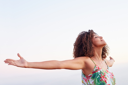 Photo pour Woman outdoors with her arms outstretched and her eyes closed expressing serene freedom - image libre de droit
