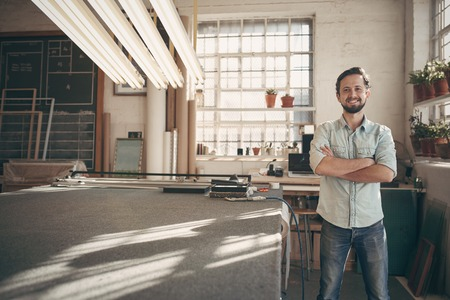Foto de Portrait of a good looking male designer standing in his workshop studio with his arms folded and smiling confidently at the camera - Imagen libre de derechos