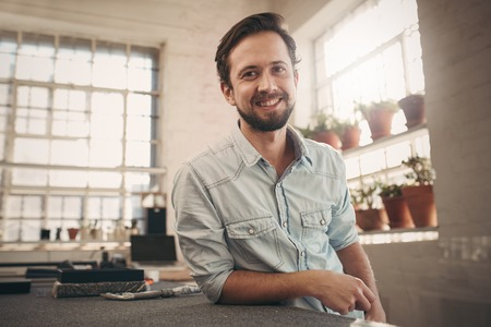Photo pour Portrait of a young male designer leaning on his workbench and giving the camera a relaxed and friendly smile - image libre de droit