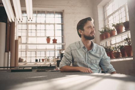 Photo pour Handsome young male small business owner sitting in his studio workshop thinking positively while looking away into the distance - image libre de droit