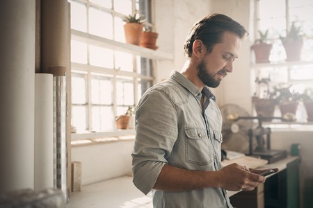 Photo pour Handsome businessman in casual wear looking at his phone while standing in the gentle light of his workshop studio - image libre de droit