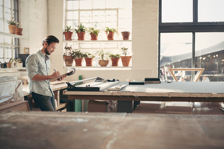 Foto de Young male business owner standing in his studio workshop checking figures and stock on his clipboard on a sunny afternoon - Imagen libre de derechos