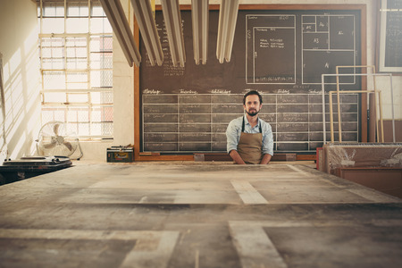 Photo pour Handsome carpeter businessman sitting in his workshop in front of a daily schedule drawn on a chalk board, looking confidently at the camera - image libre de droit