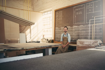 Photo pour Portrait of handsome carpenter craftsman smiling at the camera while leaning against his workbench in his workshop - image libre de droit