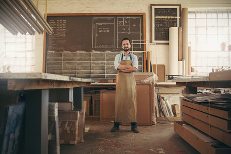 Photo pour Full length portrait of a desigern craftsman confidently standing with his arms crossed in his workshop and smiling at the camera - image libre de droit