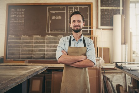 Photo pour Portrait of a designer craftsman standing in his workshop studio with his arms folded and smiling positively at the camera - image libre de droit