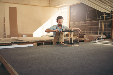 Photo pour Carpenter's workshop with a craftsman building a display case from wood and glass - image libre de droit