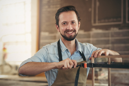 Photo pour Portrait of a craftsman using a tool to manufacture a woodwork project in his workshop - image libre de droit