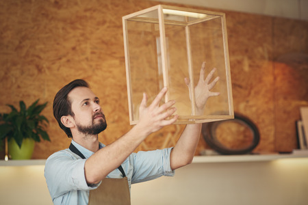Photo pour Craftsman holding up a glass and wood display case that he designed and manufactured with skill - image libre de droit