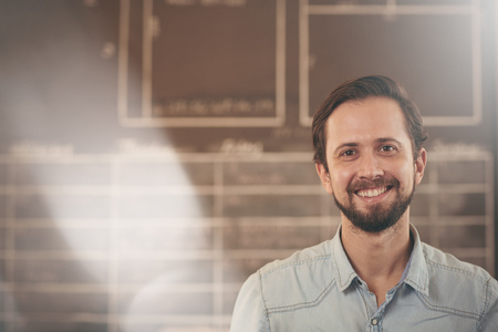 Photo pour Head and shoulders portrait of a handsome craftsman and designer in his studio smiling at the camera - image libre de droit