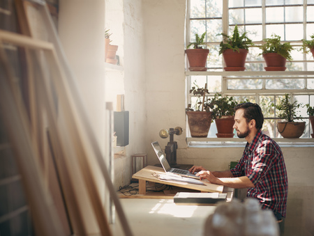 Photo pour Young male designer sitting and working on his laptop in an office space in his creative design studio - image libre de droit