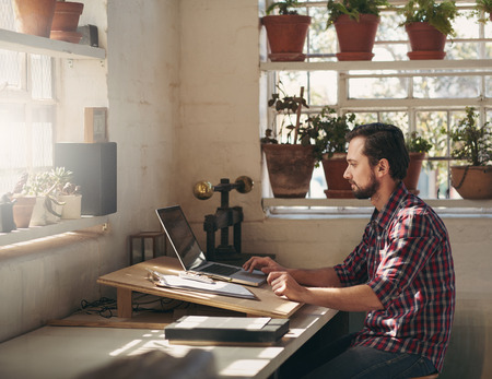 Photo pour Young designer typing on his laptop while sitting in a creative space that he uses as his office in his studio - image libre de droit