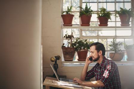 Photo pour Designer looking positive while talking on his phone at his desk in his studio - image libre de droit