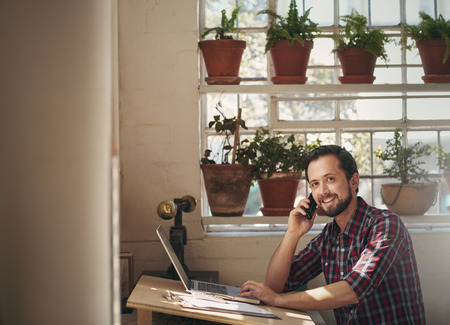 Photo pour Male designer working at his studio desk while talking on the phone and looking up to smile at the camera - image libre de droit