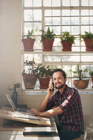 Photo pour Smiling entrepreneur sitting at the desk of his studio office and looking pleasantly at the camera while listening to his cell phone - image libre de droit