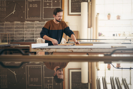 Photo pour Young professional framer using specialised tools in his workshop studio while concentrating on craftsmanship - image libre de droit