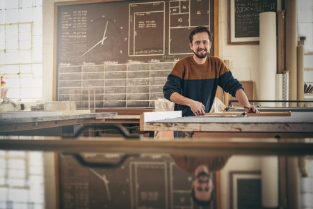 Photo pour Skilled craftsman looking up from his work and smiling while standing in his studio busy with a woodwork project - image libre de droit