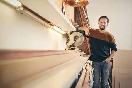 Photo pour Young professional framer posing alongside a specialised tool in his workshop looking proud and smiling happily - image libre de droit