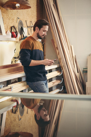 Photo pour Designer craftsman looking casual and using his phone to send a message while standing in his studio workshop - image libre de droit