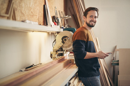Photo pour Young man using his phone and looking up with a smile while standing casually in his carpentry workshop - image libre de droit