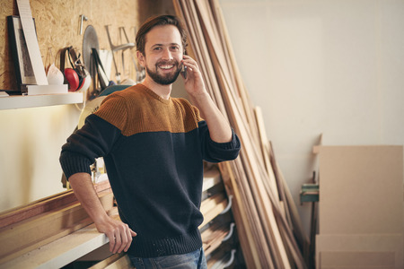 Photo pour Portrait of a young man smiling while talking on his phone and standing casually in his woodworking workshop - image libre de droit
