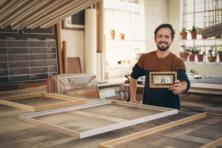 Photo pour Young entrepreneur smiling proudly in his workshop while holding up a framed bank note - image libre de droit