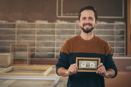 Photo pour Smiling craftsman entrepreneur standing proudly in his workshop and displaying a bank note that has been carefully framed - image libre de droit