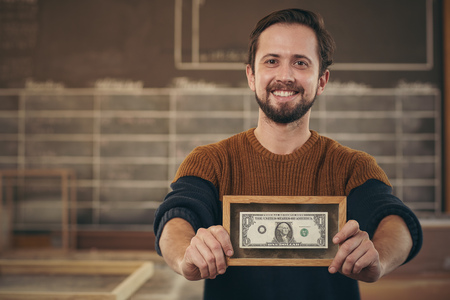 Photo pour Smiling entrepreneur standing proudly in his workshop and showing you a bank note that has been framed - image libre de droit