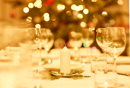 Foto de Table prepared for a family celebration dinner with a tradtional Christmas tree in the background - Imagen libre de derechos