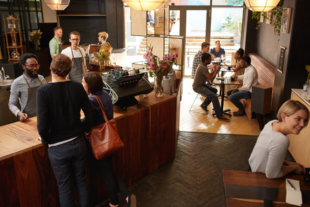Photo pour High angle shot of a couple ordering at a wooden counter in a modern coffee shop with a hipster style - image libre de droit
