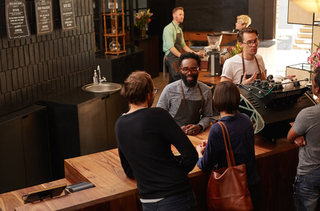 Photo pour Handsome Afro-American man working as a professional barista in a modern coffee shop - image libre de droit
