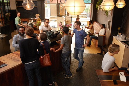 Customers being helped by professional baristas while standing at a wooden counter placing their orders