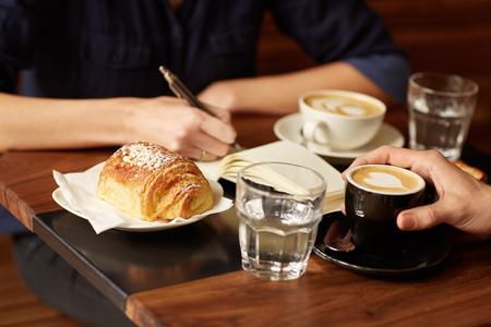 Foto de Cropped shot of two people sitting opposite each other in a coffee shop - Imagen libre de derechos