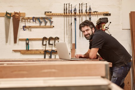 Photo pour Portrait of a middle-aged artisan in his woodwork workshop with tools on the wall, leaning on his workbench and smiling at the camera while using a laptop - image libre de droit