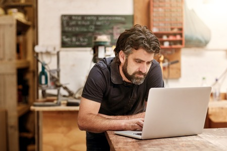 Photo for Male designer and craftsman with a rugged beard, working on his laptop at his workbench, in his studio workshop - Royalty Free Image