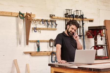 Photo for Small business owner standing in his carpentry workshop, smiling while talking on the phone, and looking at his laptop which is resting on his workbench, with tools in rows on the wall behind him - Royalty Free Image