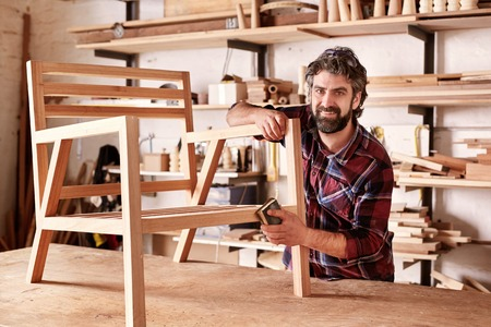Photo for Portrait of an artisan designer, with new piece of furniture, finishing off the sanding of the chair in his studio, with shelves of wood behind him - Royalty Free Image