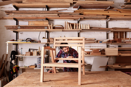 Artisan furniture designer and carpenter in his woodwork studio, with shelves of pieces of wood, while working at his workbench, carefully sanding a chair frame