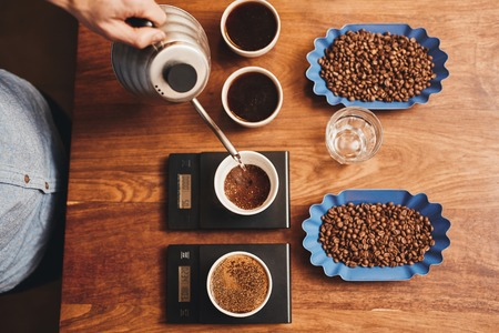 Photo pour Overhead shot of a professional barista pouring hot water from a stainless steel kettle into a cup with ground coffee, testing for a perfect cup while it is resting on digital scale on a wooden table - image libre de droit