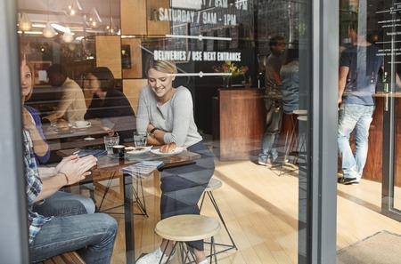 Photo pour Young woman sitting at a high table in a busy modern cafe, smiling while enjoying coffee with frineds on a lunch break - image libre de droit