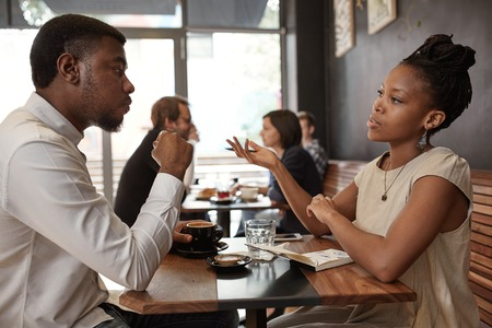 Photo pour African businesswoman and businessman sitting at a small table in a busy modern cafe, discussing ideas over coffee - image libre de droit
