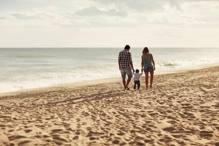 Foto de Couple and their toddler walking away from the camera along a peaceful beach - Imagen libre de derechos